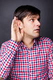 Young man listening with hand on ear Stock Photo
