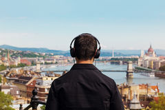 Young man listening music back view with Budapest Royalty Free Stock Images