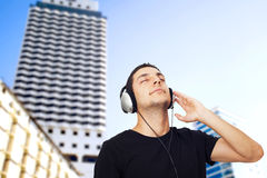Young man listening music in city Royalty Free Stock Images