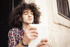 Young man listening music with digital tablet. Young man listening music with the digital tablet Royalty Free Stock Photography