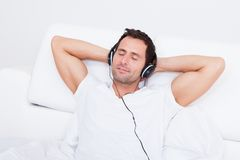Young Man Listening Music On Headphone. Indoors Royalty Free Stock Photos