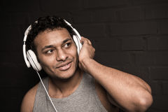 Young man listening music in headphones, isolated on black Stock Photo