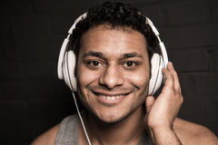 Young man listening music in headphones, isolated on black Stock Photos
