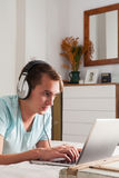 Young man listening music with headphones lying the bedroom. Royalty Free Stock Images