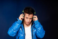 Young man listening music with headphones portrait. On blue ligh background Royalty Free Stock Photo