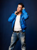 Young man listening music headphones standing. Young man listening music with headphones standing on blue ligh background stock photos