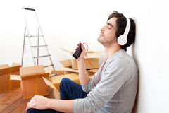 Young man listening music after moving in his new flat. View of a Young man listening music after moving in his new flat Royalty Free Stock Photos