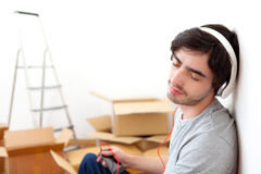 Young man listening music after moving in his new flat. View of a Young man listening music after moving in his new flat Royalty Free Stock Images