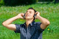 Young man listening music outdoors Stock Photography