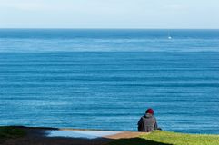 Young man listening music is sitting on cliff`s edge of the sea royalty free stock photography