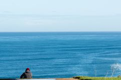 Young man listening music is sitting on cliff`s edge of the seain a spring day stock photo