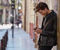 Young man listening music smartphone earphones Stock Images