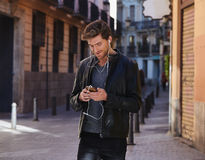 Young man listening music smartphone earphones Royalty Free Stock Photos