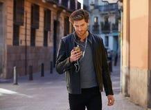Young man listening music smartphone earphones Stock Photo