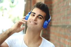 Young man listening something. Outdoors. stock photo