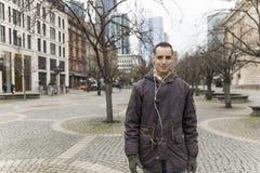 Young Man Listening to Earphones in Pedestrian Zone Walking Towards Camera