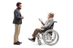 Young man listening to an elderly gentleman sitting in a wheelchair and talking stock image