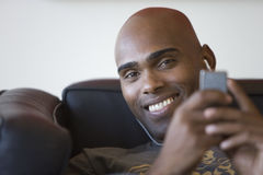 Young man listening to mp3 player on sofa, smiling, portrait, close-up Stock Image