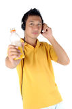 Young man listening to music. While brandishing his drink bottle, isolated on white Royalty Free Stock Images
