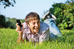 Young Man Listening to Music. Young Man Lying on Grass, Listening to Music Royalty Free Stock Photo