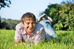 Young Man Listening to Music. Young Man Lying on Grass, Listening to Music Stock Photography