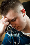 Young Man Listening to Music. A young man is listening to music through hie ear buds from a digital music player Royalty Free Stock Photography