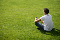 Young man listening to music. Young man sitting on the grass listening to his mp3 player. View from behind Royalty Free Stock Photo
