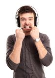 Young man listening to music and biting a wire Royalty Free Stock Photos