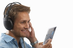 young man listening to music on earphones, cut out Royalty Free Stock Image