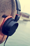 Young man listening to music in front of the sea Stock Photos