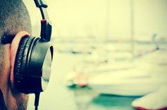 Young man listening to music  in front of the sea, with a filter Royalty Free Stock Images