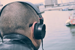 Young man listening to music in front of the sea, filtered Royalty Free Stock Image