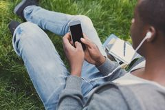 Young man listening to music on grass outdoors. Young unrecognizable african-american man sitting on grass, using smartphone and listening to music with Stock Image