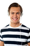 Young man listening to music through headphones Stock Photo
