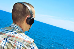 Young man listening to music with headphones in front of the sea Stock Image