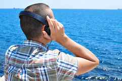 Young man listening to music with headphones in front of the sea Royalty Free Stock Photo