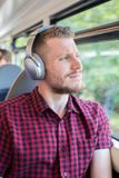 Young Man Listening To Music On Headphones During Journey To Wor Royalty Free Stock Images