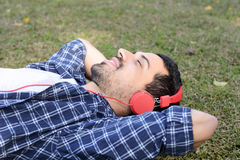 Young man listening to music with headphones in park. Royalty Free Stock Images