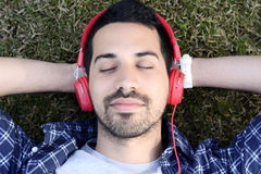 Young man listening to music with headphones in park. Stock Photos