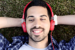 Young man listening to music with headphones in park. Royalty Free Stock Photos