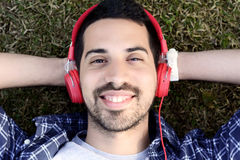Young man listening to music with headphones in park. Stock Photography