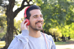 Young man listening to music with headphones in park. Royalty Free Stock Image