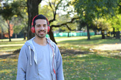 Young man listening to music with headphones in park. Stock Images