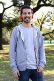 Young man listening to music with headphones in park. Stock Image