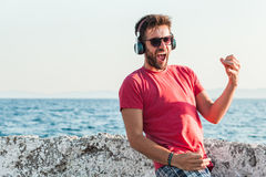 Young man listening to the music on headphones playing imaginary guitar Royalty Free Stock Images
