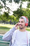 Young man listening to music with headphones sitting on park ben Royalty Free Stock Images