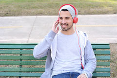 Young man listening to music with headphones sitting on park ben Stock Image