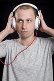 Young man listening to music in headphones with a sullen express Stock Images