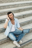 Young man listening to music with headphones via digita Royalty Free Stock Photography