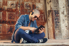 Young man listening to music with headphones via tablet Royalty Free Stock Photo